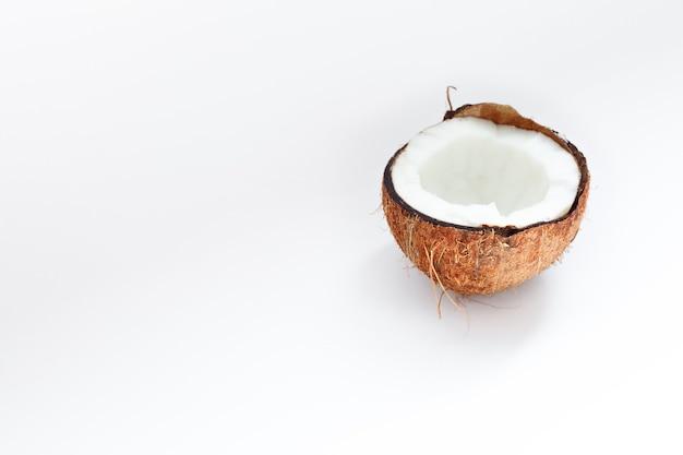 Cibo, minimalismo, colore, natura morta e concetto naturale - metà del primo piano della noce di cocco su uno sfondo bianco