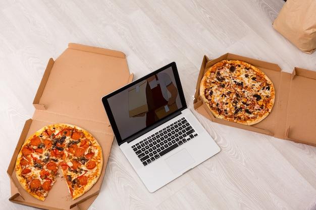 Concetto di ordine alimentare. primo piano vista dall'alto di una pizza ordinata con un computer portatile. tutta la grafica dello schermo è composta.