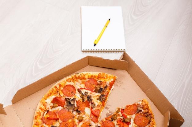 Concetto di ordine alimentare. primo piano vista dall'alto di una pizza ordinata