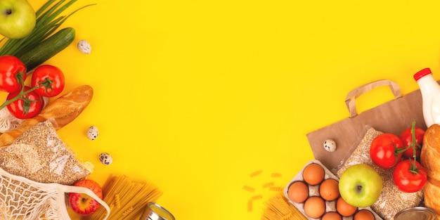 Imballaggi alimentari su sfondo giallo. quarantena consegna cibo a domicilio. banner flatlay con copyspace.