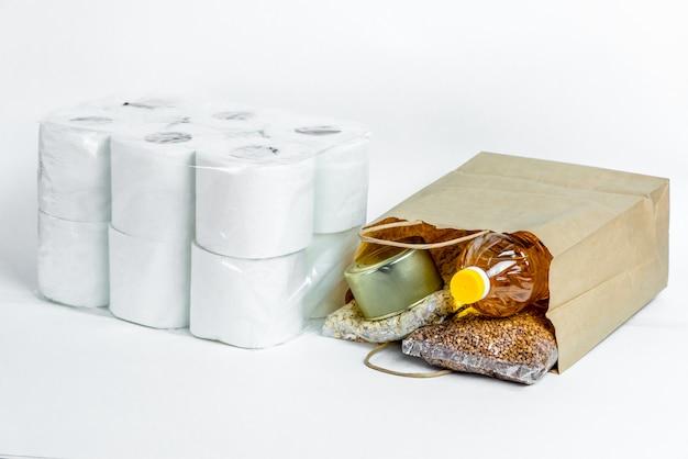 Cibo in un sacco di carta per donazioni, isolato su uno sfondo bianco. scorte anticrisi di beni essenziali per il periodo di isolamento in quarantena. consegna del cibo, coronavirus. la carenza di cibo.