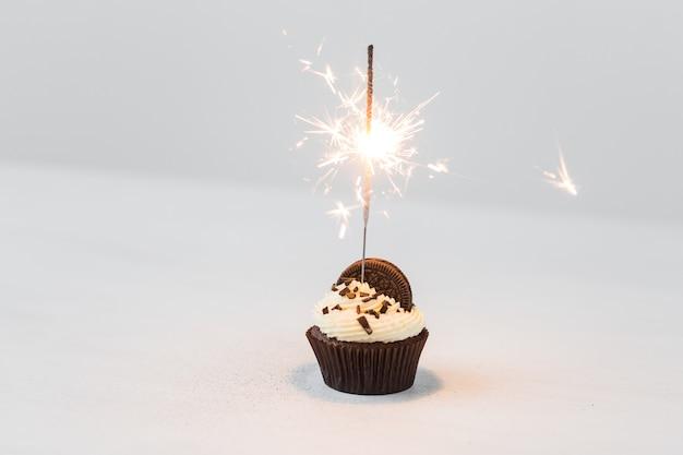 Concetto di cibo, festa e vacanza - cupcake compleanno con sparkler su uno spazio bianco