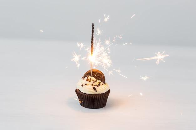 Concetto di cibo, festa e vacanza - cupcake di compleanno con sparkler