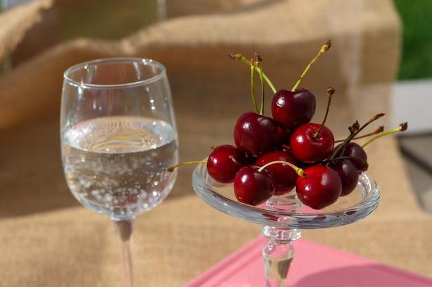 Foto del cibo il piatto di servizio con piedi e la mini cupola con bacche di ciliegia sono sul libro e su tela