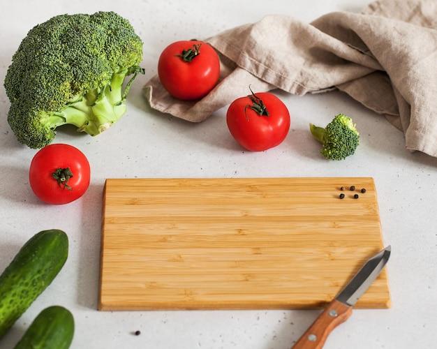 Foto di cibo con tagliere vuoto per il testo con un coltello pomodori, broccoli e cetrioli