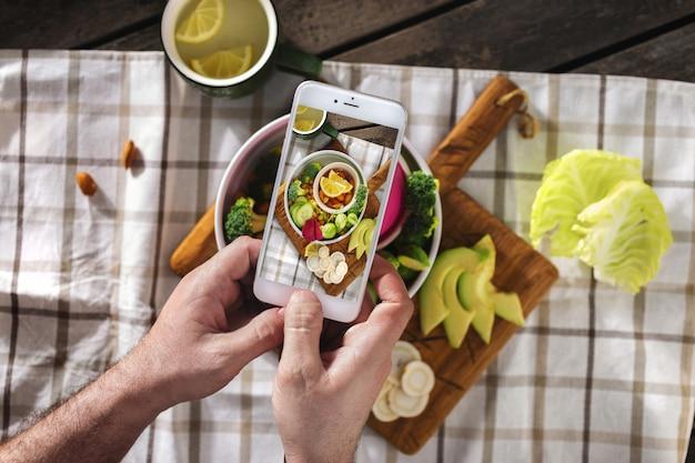 Fotografia di cibo al telefono. concetto di contenuto di blog alimentari. le mani maschii prendono la foto del piatto del vegano con la vista superiore del telefono dello schermo