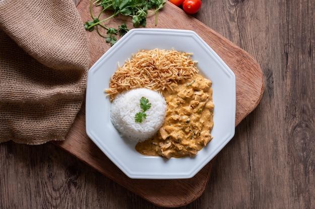 Piatto di cibo con pollo alla stroganoff sulla tavola di legno.