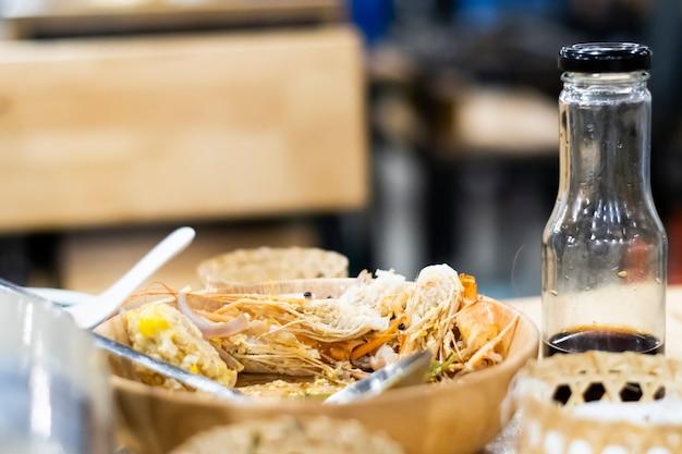 Avanzi di cibo in un piatto di legno sdraiato sul tavolo da pranzo.