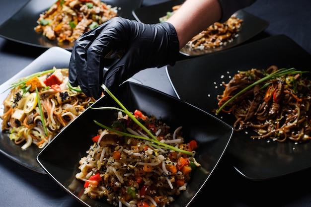 Stilista di cibo o blogger che decora il pasto asiatico per la presentazione. concetto di business per il tempo libero hobby arte. mano della donna in guanti di lattice neri