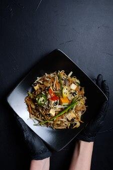 Stilista di cibo o blogger che tiene pasto orientale in un piatto nero su sfondo scuro. concetto di arte hobby per il tempo libero. mano della donna in guanti di lattice neri. concetto di spazio libero