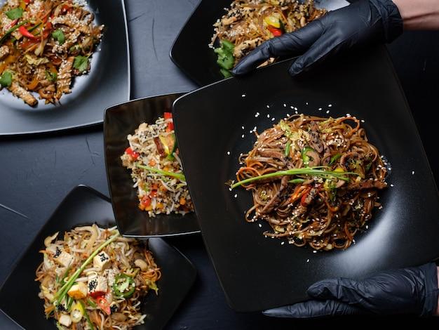 Stilista del cibo che prepara pasti orientali per presentazioni o servizi fotografici pubblicitari. concetto di arte hobby per il tempo libero. mano della donna in guanti di lattice neri che tengono un piatto