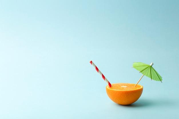 Concetto minimo di cibo estivo. succo d'arancia e succosi frutti tropicali su uno sfondo di colore chiaro