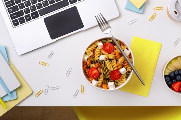 Cibo in scatole da asporto sul tavolo bianco con il computer portatile. consegna di cibo in linea.
