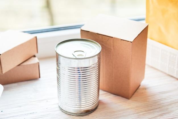 Latta dell'alimento imballata in contenitore di cartone, concetto di consegna dell'alimento