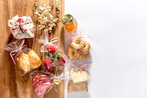 Vista dall'alto dell'alimento su fondo di legno mezzo bianco mezzo. salame, fragole, cracker, pasticcini, pane e miele.