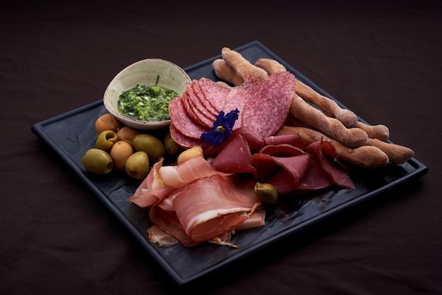 Vassoio di cibo con delizioso salame, pezzi di prosciutto affettato, salsiccia