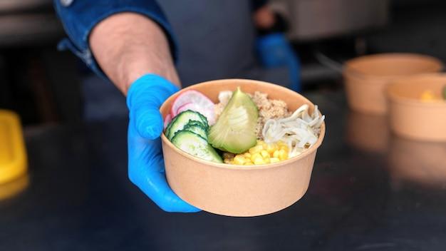 Food truck, cuoco consegna l'ordine finito, piatto con insalata