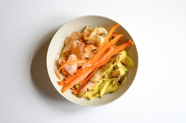 Rifiuti alimentari da cucina domestica, pulizia da verdure cipolle patate e carote in un piatto su un tavolo bianco. smistamento dei rifiuti alimentari domestici