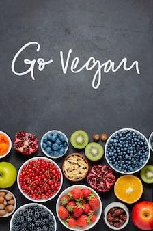 Alimenti ad alto contenuto di antiossidanti: bacche, noci, frutta. sfondo di cemento nero. iscrizione manoscritta: vai vegan.