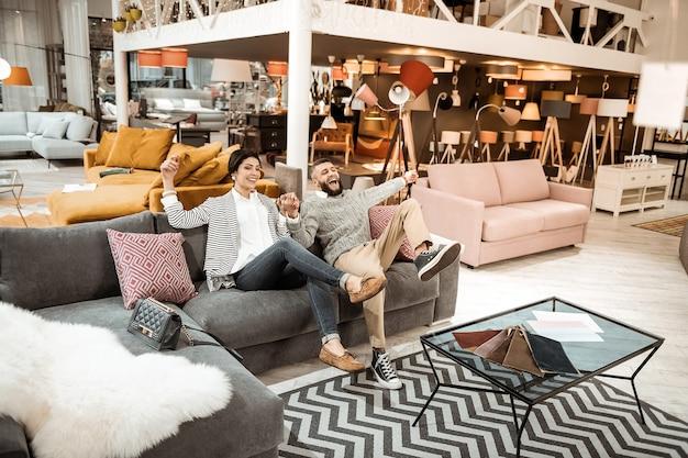 Scherzare. coppia adulta estremamente piacevole che è felice della propria vita e che agisce liberamente nel negozio di mobili