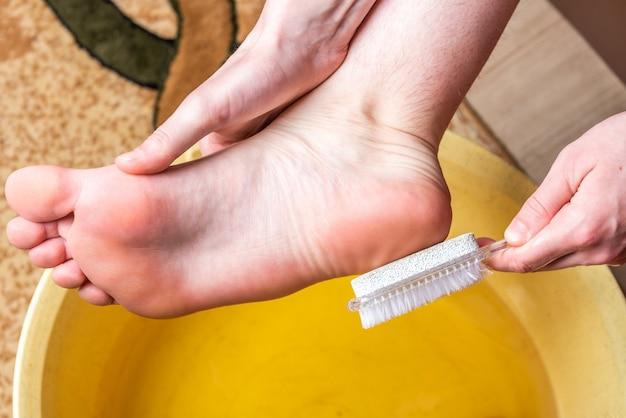 Pediluvi. prenditi cura della pelle secca di piedi e talloni. utilizzando strumenti di pomice per pedicure e un pennello.