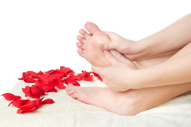 Cura dei piedi. bei piedini femminili e petali di rosa