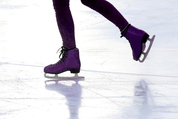 Persona di pattinaggio sul ghiaccio del piede sulla pista alla luce del sole. sport e hobby in vacanza