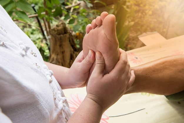 Massaggio ai piedi o riflessologia plantare thailandese per la salute nella natura.
