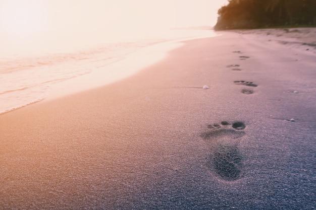 Stampa del piede sulla spiaggia sul fondo del mare di alba con filtro vintage