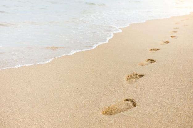 Stampa del piede sulla sabbia sullo sfondo spiaggia