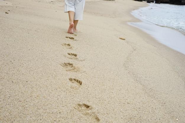 Impronte di piedi sulla sabbia della spiaggia