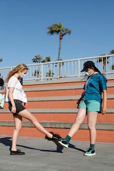 Saluto del tremolio dei piedi, adolescenti all'aperto nella nuova normalità