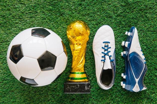 Sfondo di calcio su erba con trofeo tra palla e scarpe