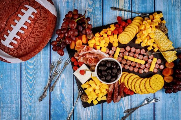 Pallone da calcio a base di formaggio e salsiccia per tagliere di salumi su legno. concetto di gioco del football americano.
