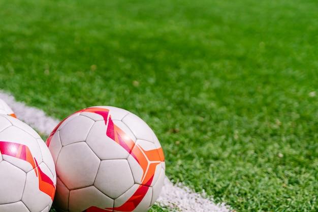 Palloni da calcio su un pich. sfondo di calcio con copia spazio.
