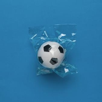 Un pallone da calcio in una confezione di cellophan su sfondo blu. il concetto di un gioco popolare.