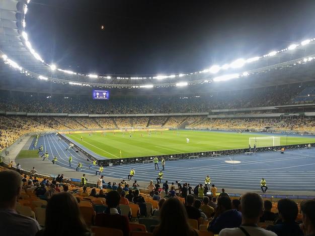 Competizione di calcio in un grande stadio la sera con un punto culminante luminoso rimosso dagli spalti