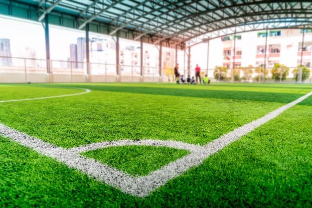 Linea bianca dell'angolo di calcio sull'erba verde del manufatto del campo dell'interno di calcio.