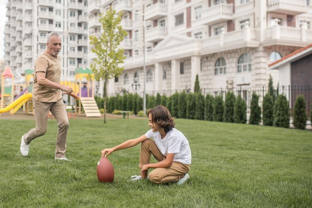 Calcio. ragazzo dai capelli scuri in una maglietta bianca che gioca a calcio
