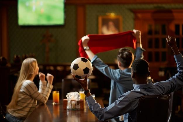 Appassionati di calcio con sciarpa rossa guardando la traduzione del gioco, amici al bar