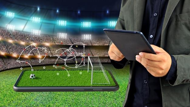 Manager di calcio con strategia di gioco su smartphone. campo da calcio