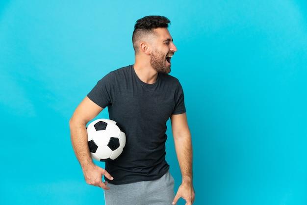 Giocatore di football isolato su sfondo blu che ride in posizione laterale