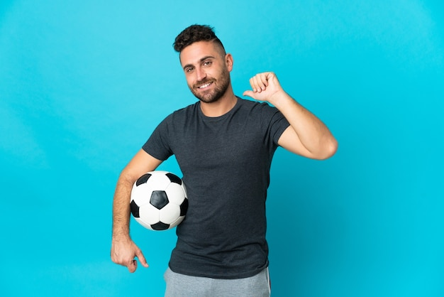 Giocatore di football isolato su sfondo blu orgoglioso e soddisfatto di sé