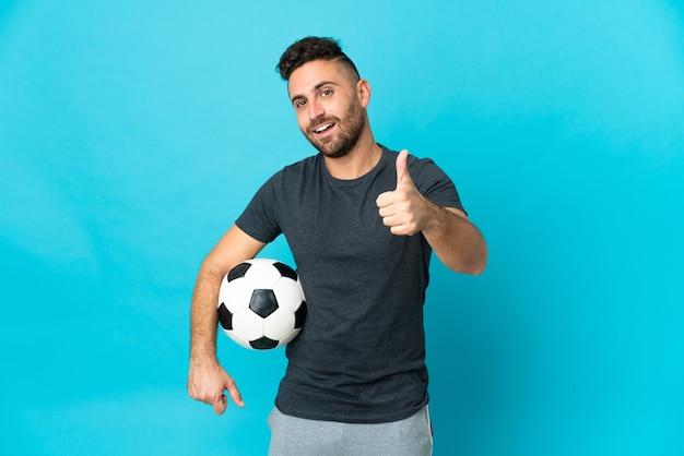 Giocatore di football isolato su sfondo blu con il pollice in alto perché è successo qualcosa di buono