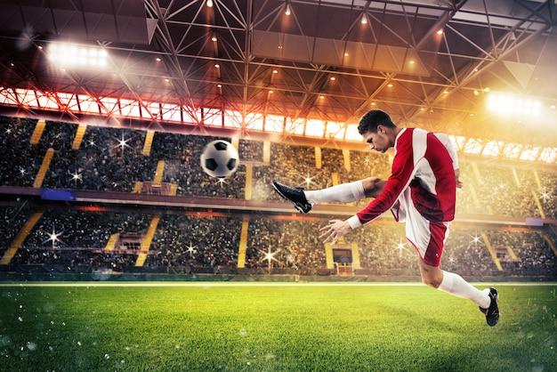 Il giocatore di football calcia il pallone nel campo di uno stadio