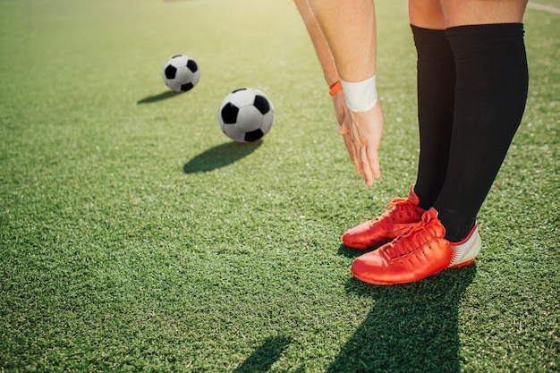 Supporto del giocatore di football americano su prato inglese e allungare giù al campo verde. tiene le gambe e le mani unite. due palloni da calcio distesi ulteriormente.