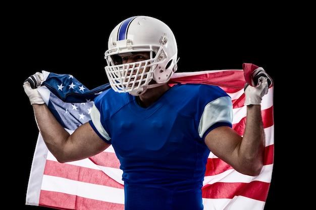 Giocatore di football americano con una divisa blu e una bandiera americana, su una parete nera