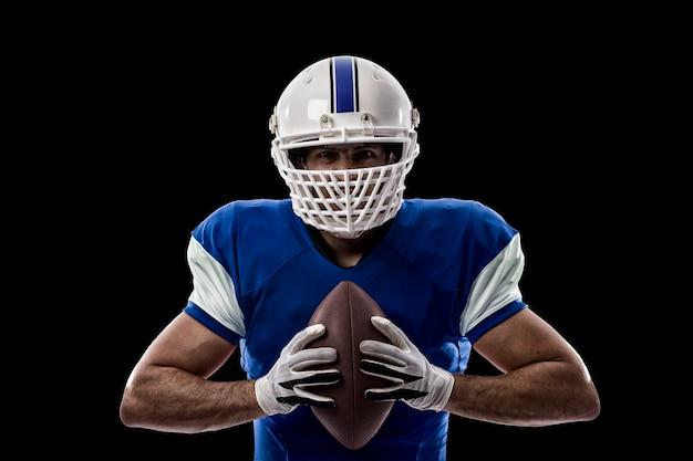 Giocatore di football americano con un'uniforme blu su una parete nera