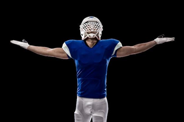 Giocatore di football americano con una divisa blu che celebra, su una parete nera
