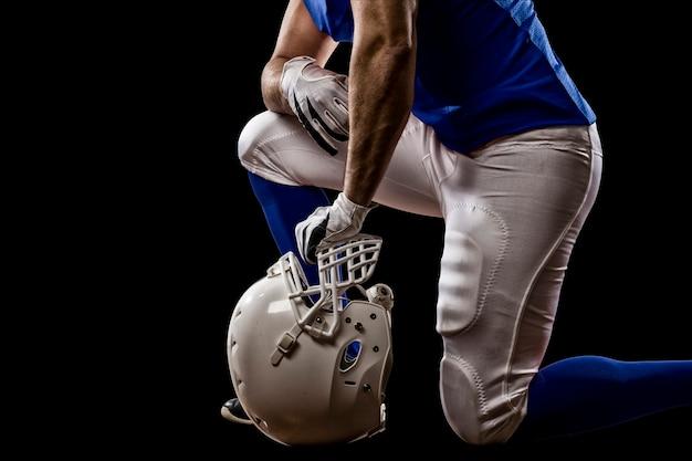 Giocatore di football con una divisa blu in ginocchio su un muro nero